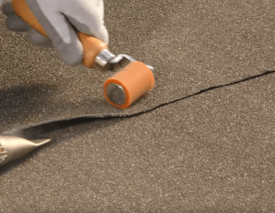 Using A Hand Roller To Secure Peel And Stick Roofing